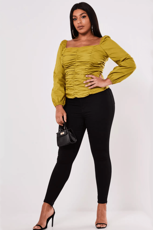 A plus-size model wearing a chartreuse long-sleeve ruched top.
