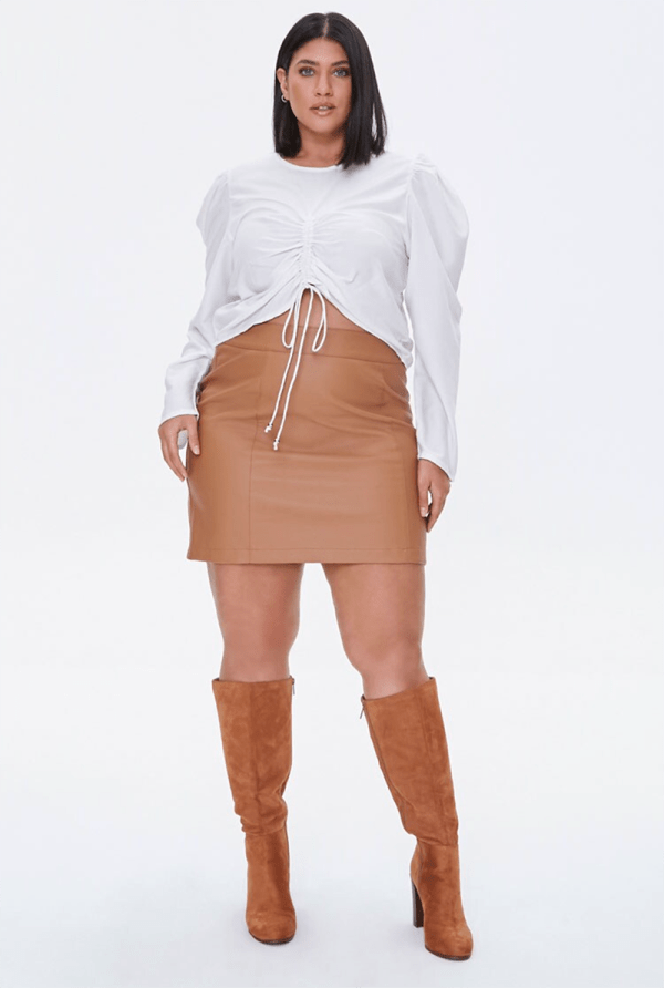 A plus-size model wearing a white long-sleeve ruched top.
