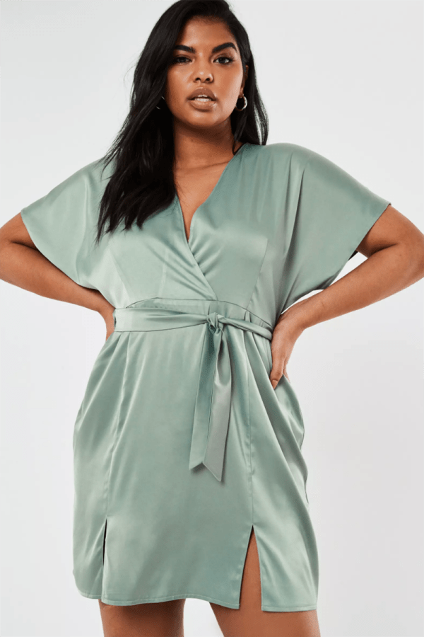A plus-size model wearing a light blue satin mini wrap dress.