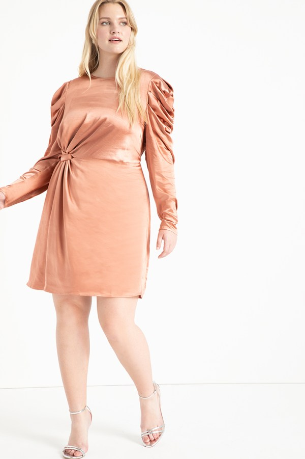A plus-size model wearing a champagne satin mini dress.