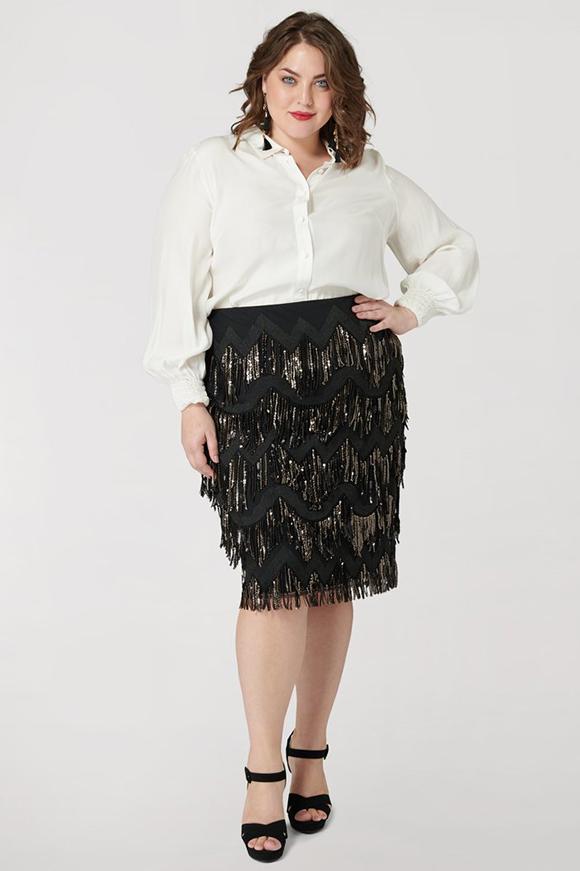 A plus-size model wearing a black sequin fringe skirt.
