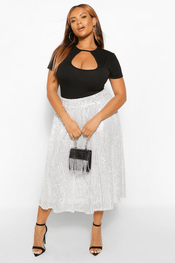 A plus-size model wearing a silver sequin circle skirt.