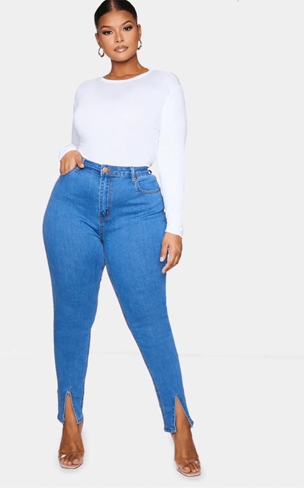 A plus-size model wearing split-hem skinny jeans.