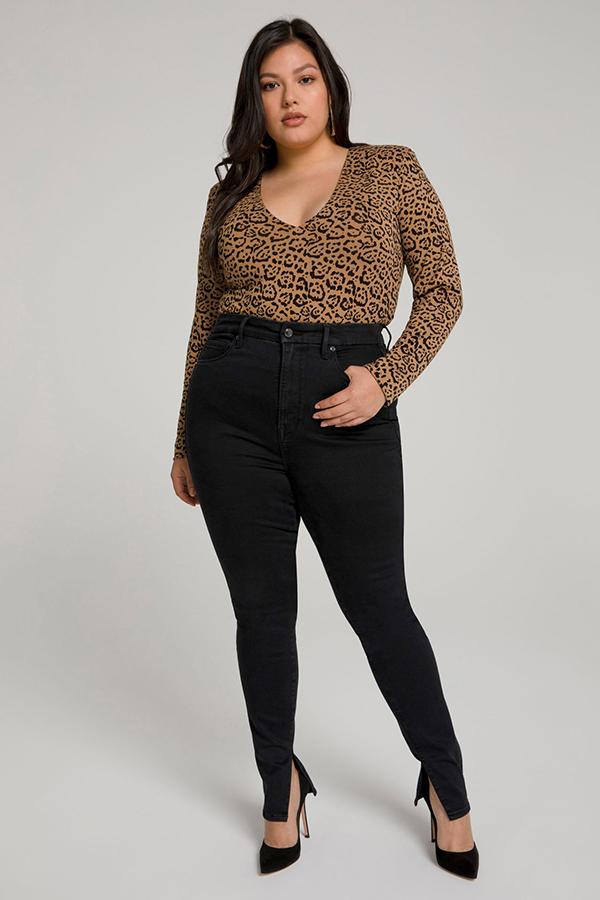 A plus-size model wearing black split-hem skinny jeans.