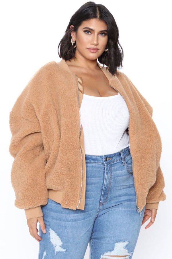 A plus-size model wearing a camel teddy bomber jacket.