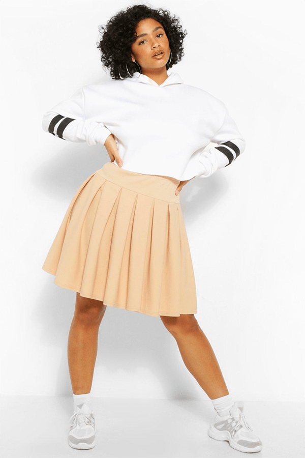 A plus-size model wearing a tan tennis skirt.