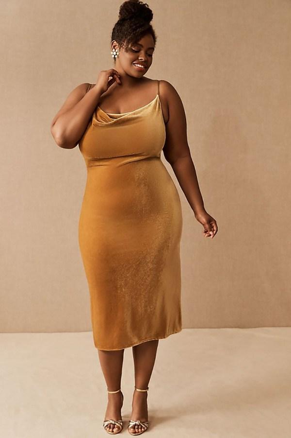 A plus-size model wearing a gold velvet slip dress.