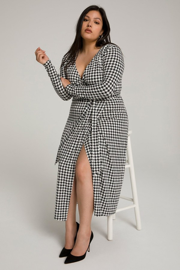 A plus-size model wearing a sexy houndstooth wrap dress.