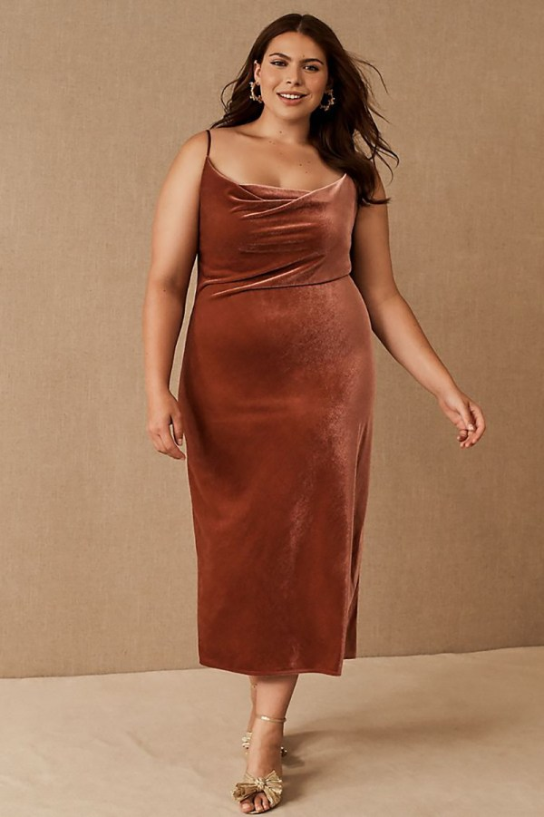 A plus-size model wearing a sexy brown velvet slip dress.