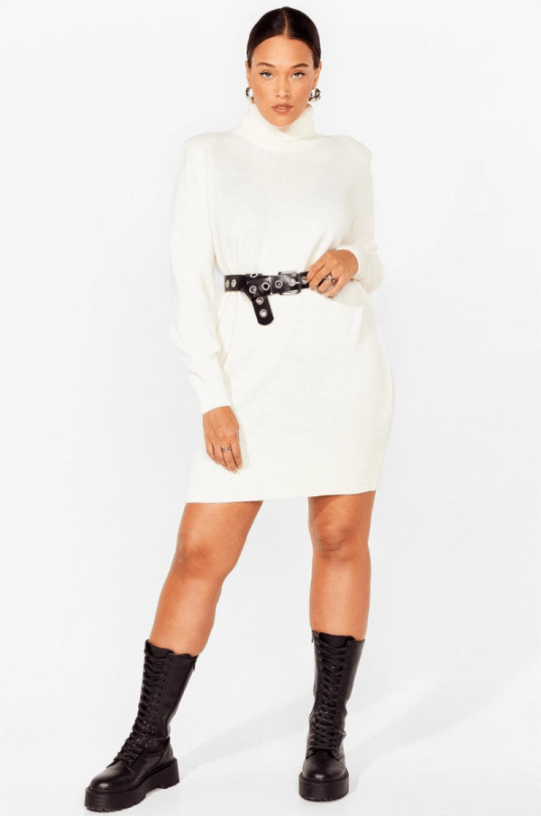 A plus-size model wearing a sexy white turtleneck sweater mini dress.