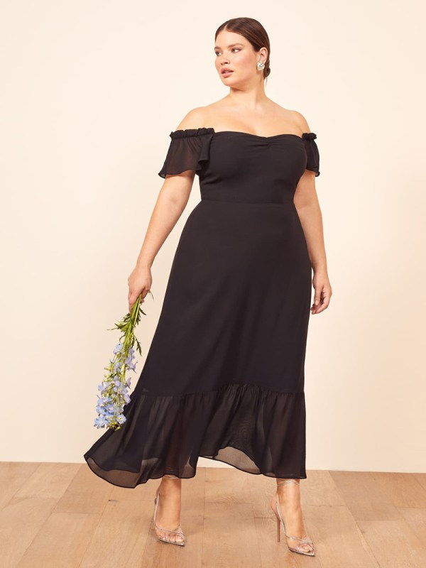 A plus-size model wearing a sexy black off-the-shoulder dress.