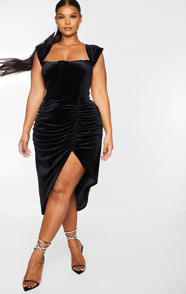 A plus-size model wearing a sexy black velvet dress.