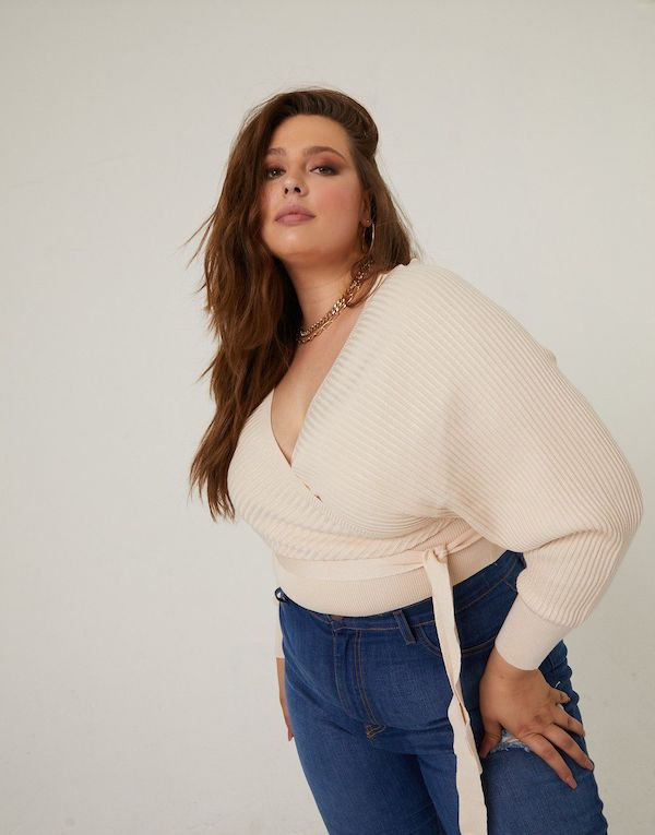 A plus-size model from 2020AVE wearing a cream wrap sweater.