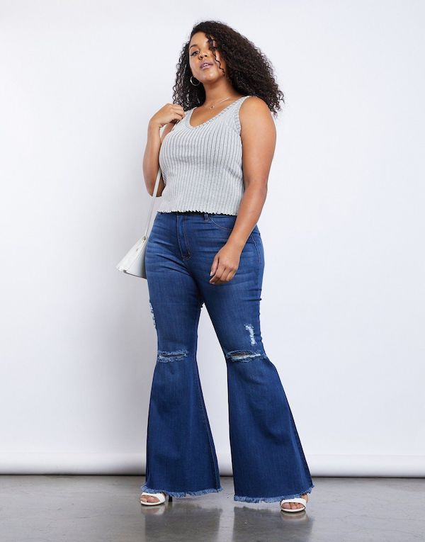 A plus-size model from 2020AVE wearing flare jeans.