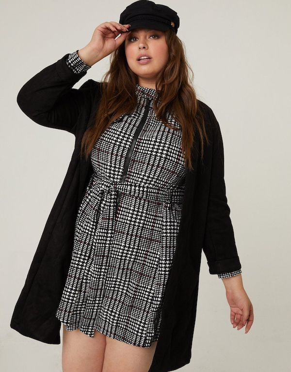 A plus-size model from 2020AVE wearing a black and white plaid mini dress.