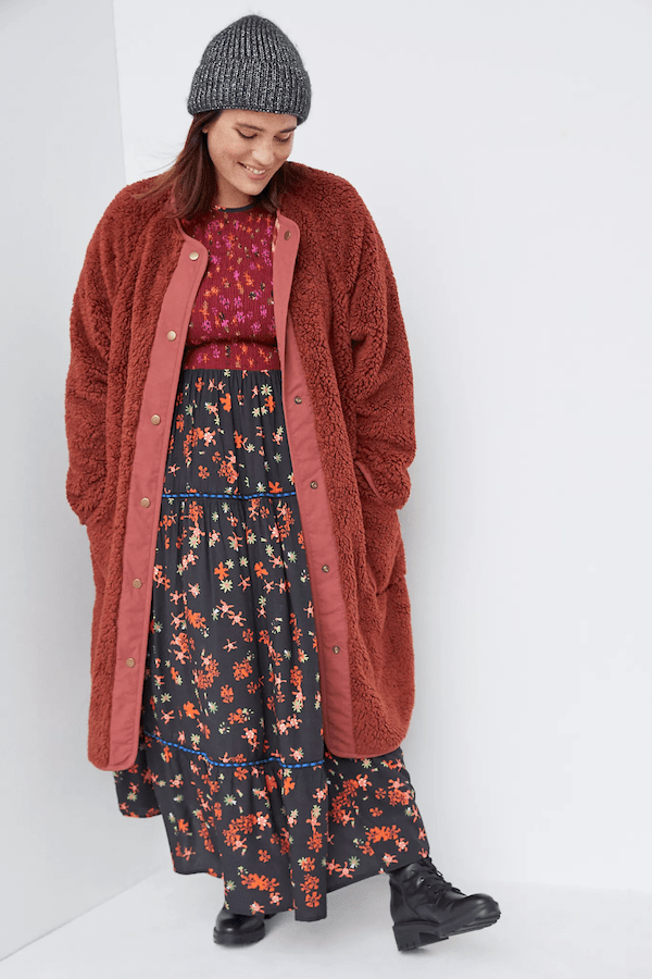 A plus-size model wearing a red fuzzy coat.