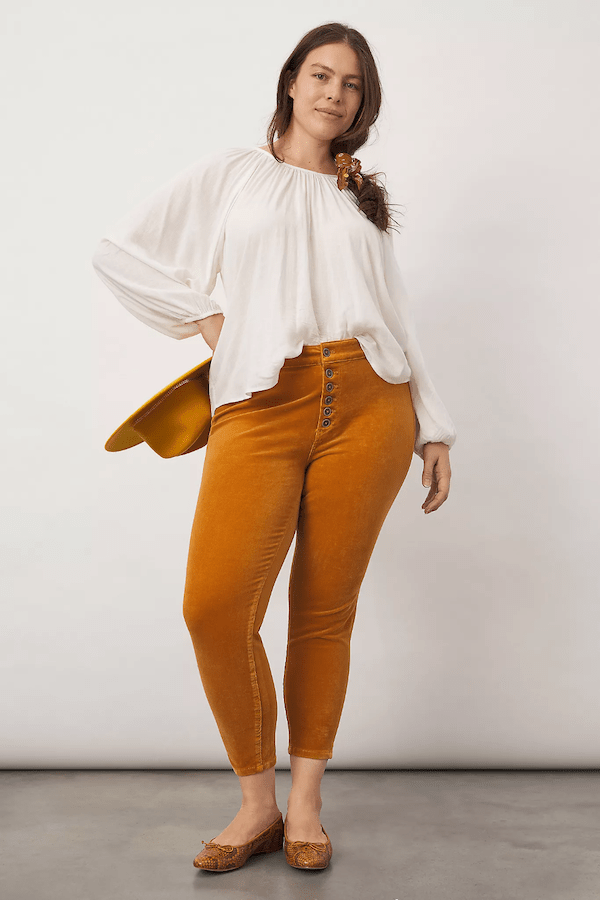 A plus-size model wearing light brown pants and a white top.