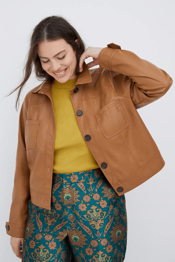 A plus-size model wearing a camel leather jacket.