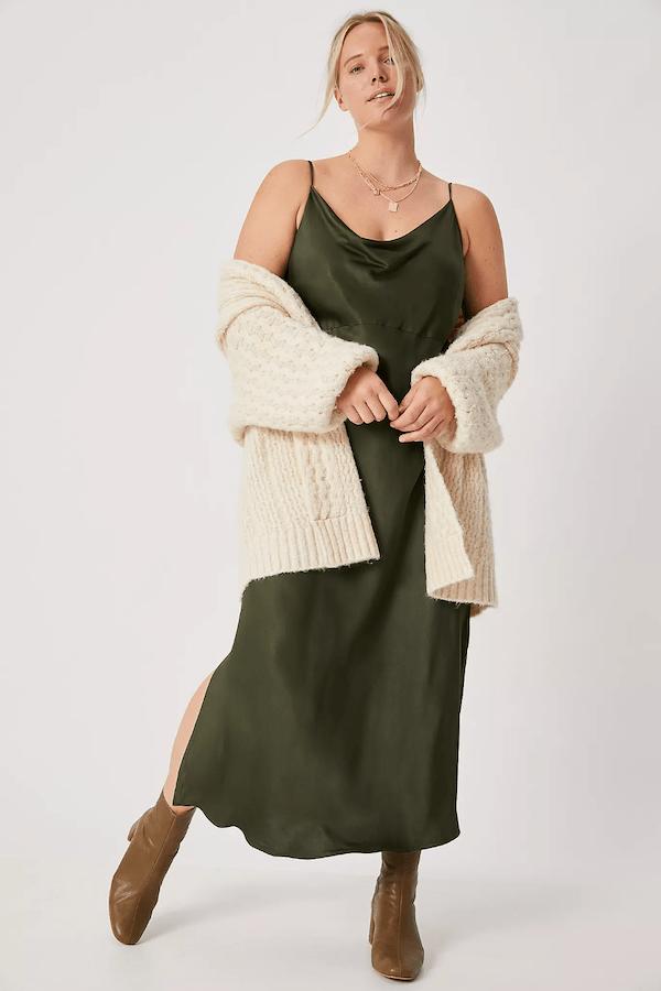 A plus-size model wearing an olive slip dress.