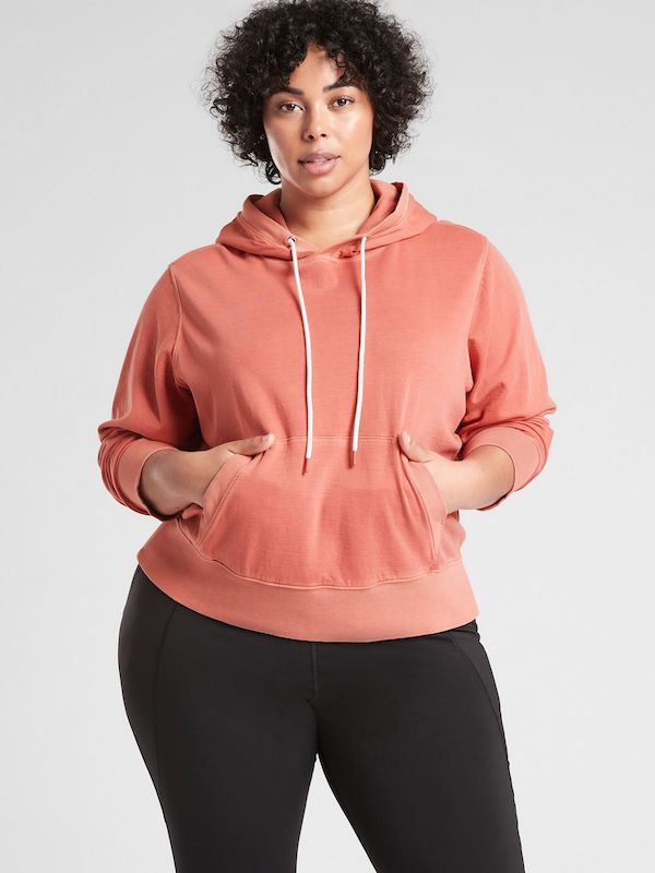 A plus-size model from Athleta wearing a melon pink hoodie.