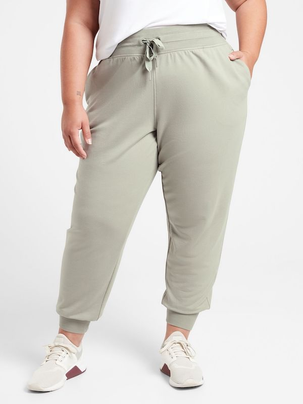 A plus-size model from Athleta wearing light green joggers.