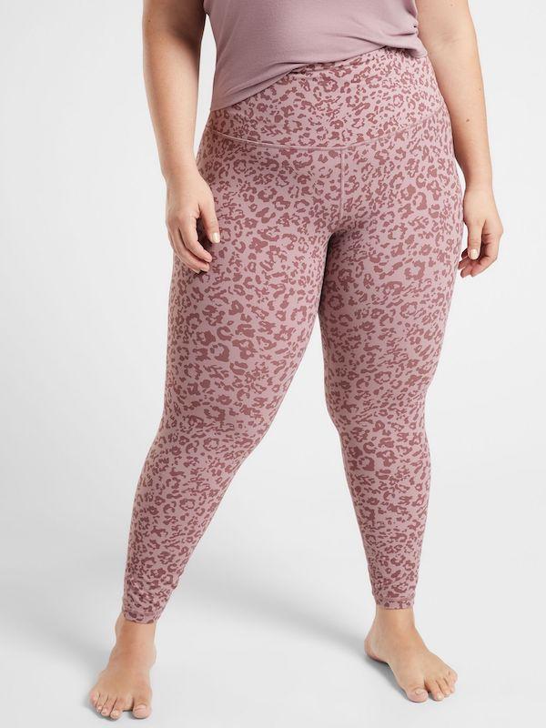 A plus-size model from Athleta wearing pink animal print leggings.