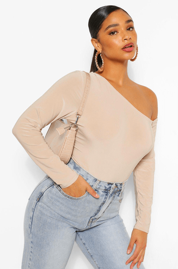 A plus-size model wearing an off-the-shoulder beige top, which will be on sale at Boohoo's 2020 Black Friday sale.