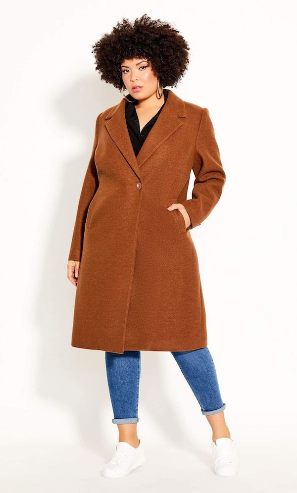 A plus-size model from CoEdition's Black Friday sale wearing a brown coat.
