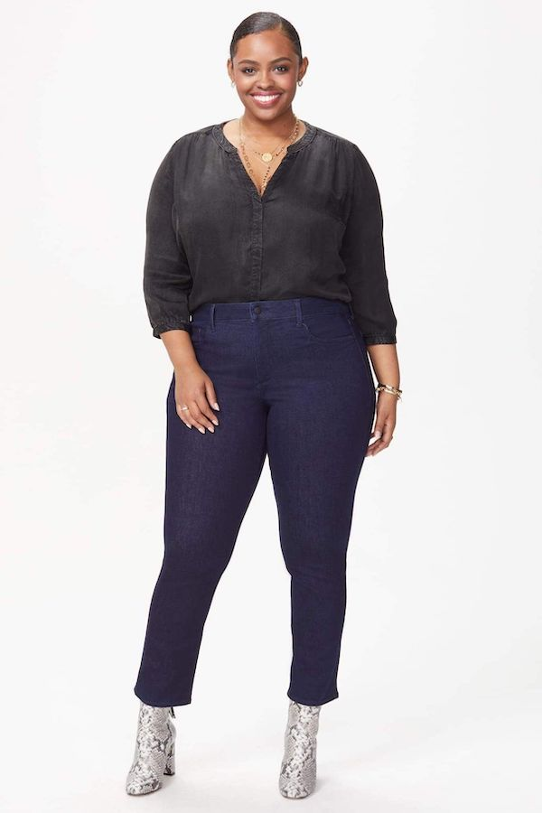 A plus-size model from CoEdition's Black Friday sale wearing high-waisted dark jeans.