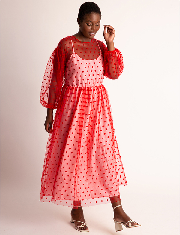 A plus-size model wearing a red polka dot mesh dress, which will be marked down at Eloquii's 2020 Black Friday sale.