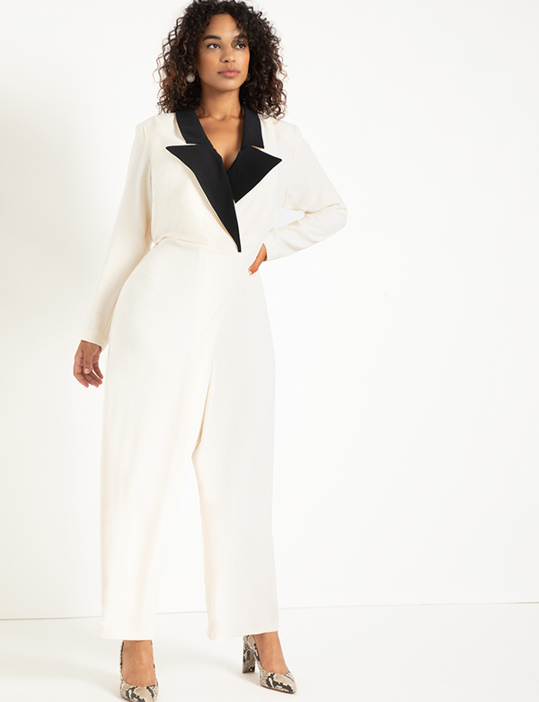 A plus-size model wearing a white tuxedo jumpsuit, which will be marked down at Eloquii's 2020 Black Friday sale.