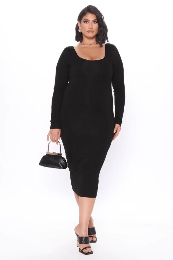 A plus-size model from Fashion Nova wearing a black bodycon midi dress.