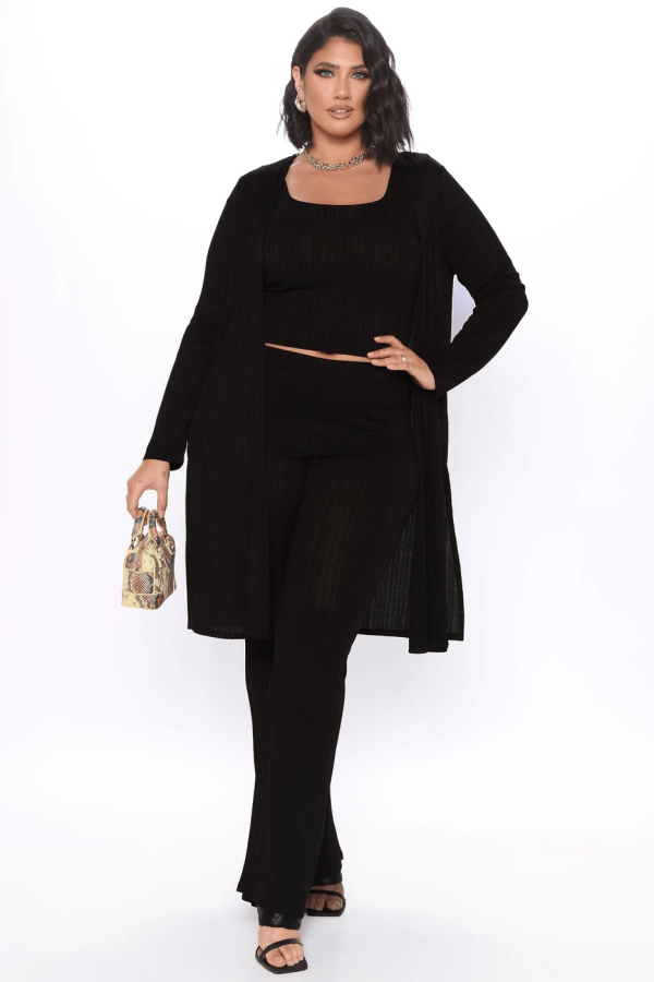 A plus-size model from Fashion Nova wearing a black top, sweater, and pants.
