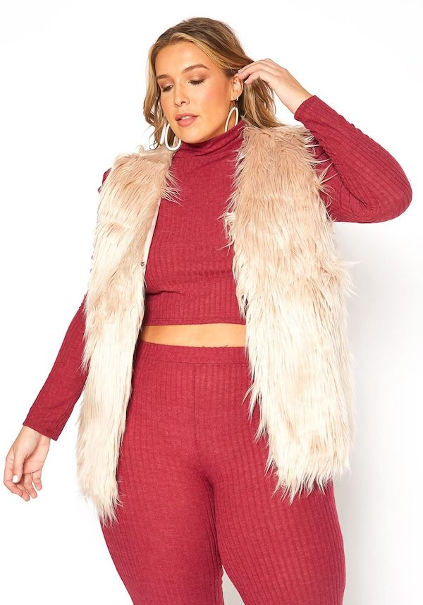 A plus-size model wearing a tan faux fur vest.