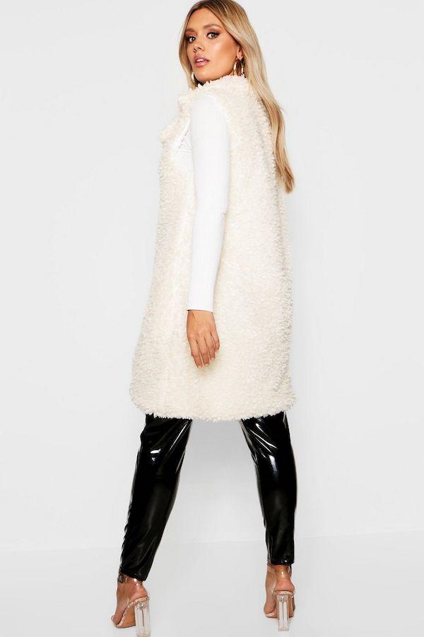 A plus-size model wearing a cream faux fur vest.
