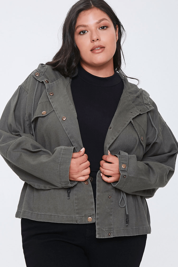 A plus-size model wearing a gray jacket.