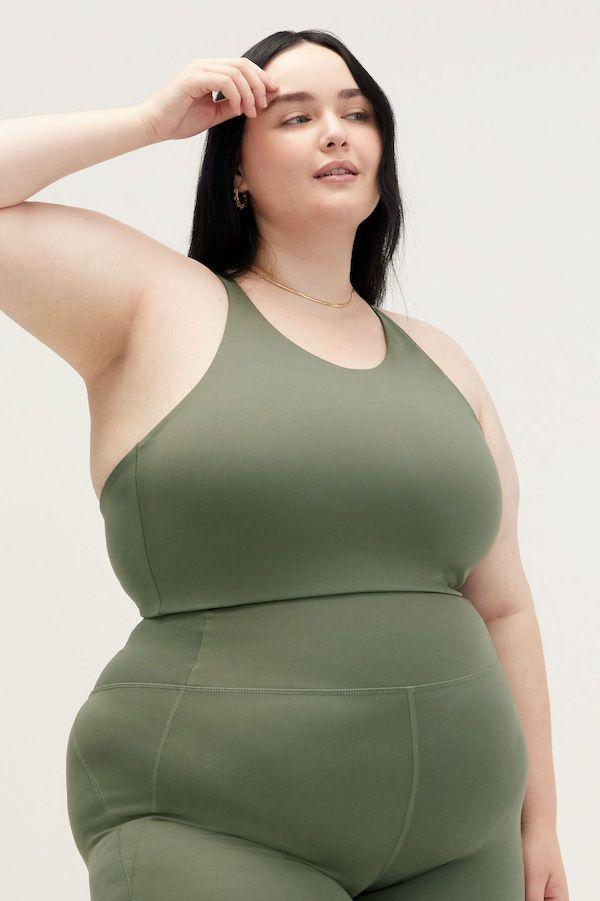 A plus-size model from Girlfriend wearing a green sports bra.