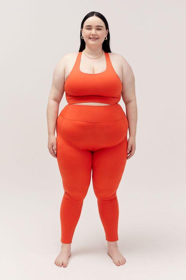 A plus-size model from Girlfriend wearing red leggings.