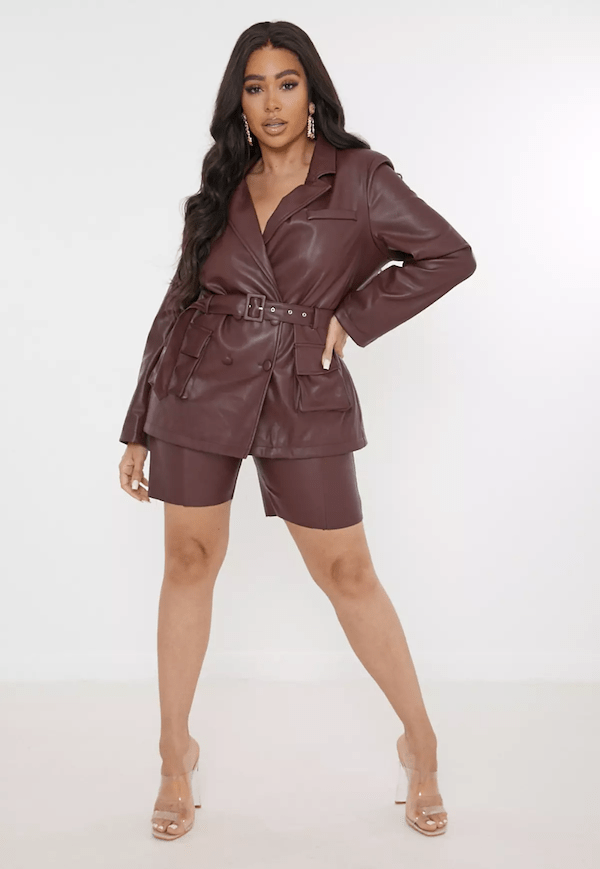 A plus-size model for Missguided wearing faux leather blazer and shorts.