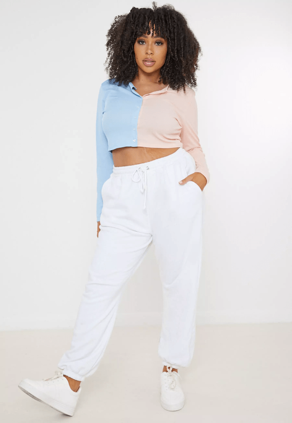 A plus-size model for Missguided wearing a blue and pink cropped sweatshirt.