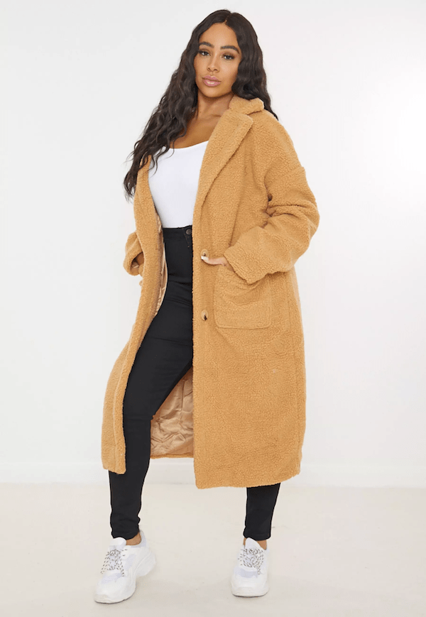 A plus-size model for Missguided wearing a faux shearling coat.