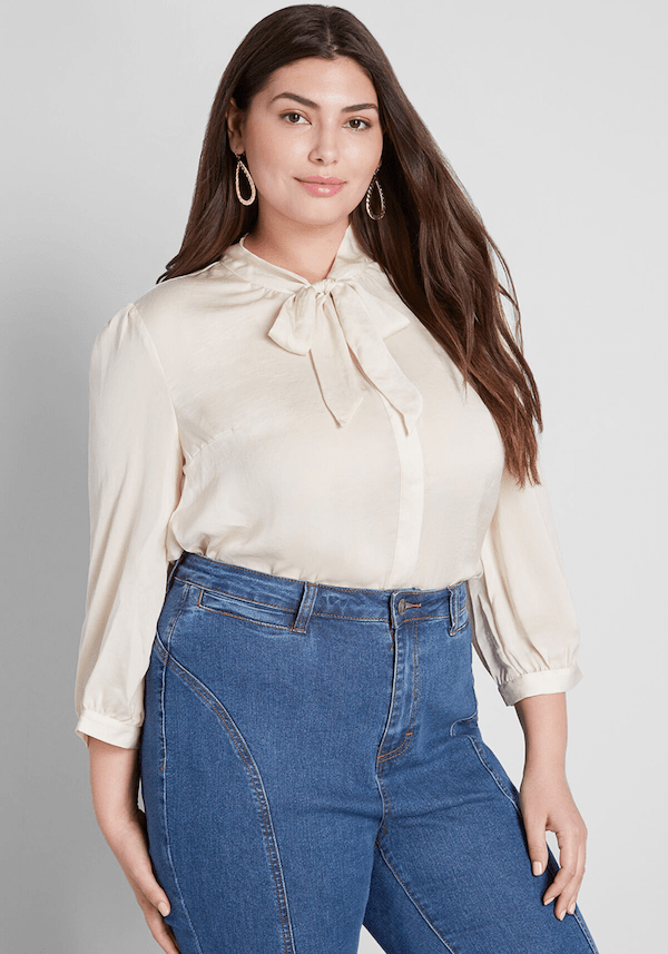 A plus-size model from ModCloth wearing a cream tie-front blouse.