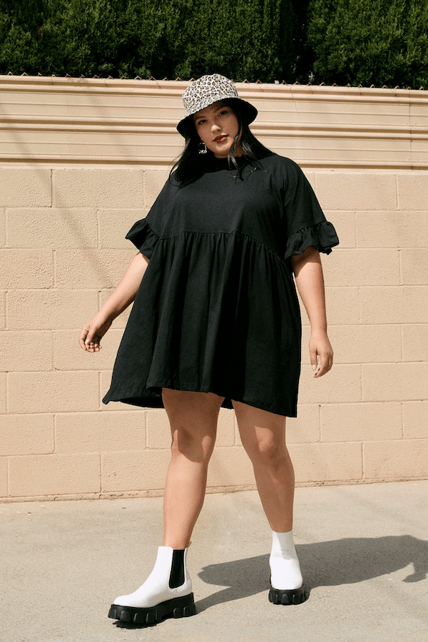 A plus-size model from Nasty Gal wearing a black mini dress.