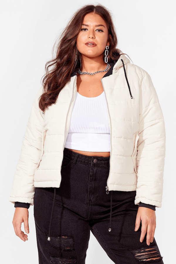 A plus-size model from Nasty Gal wearing a cream puffer jacket.
