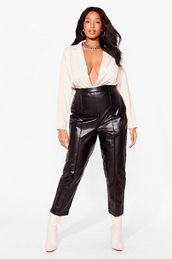 A plus-size model from Nasty Gal wearing faux leather black trousers.