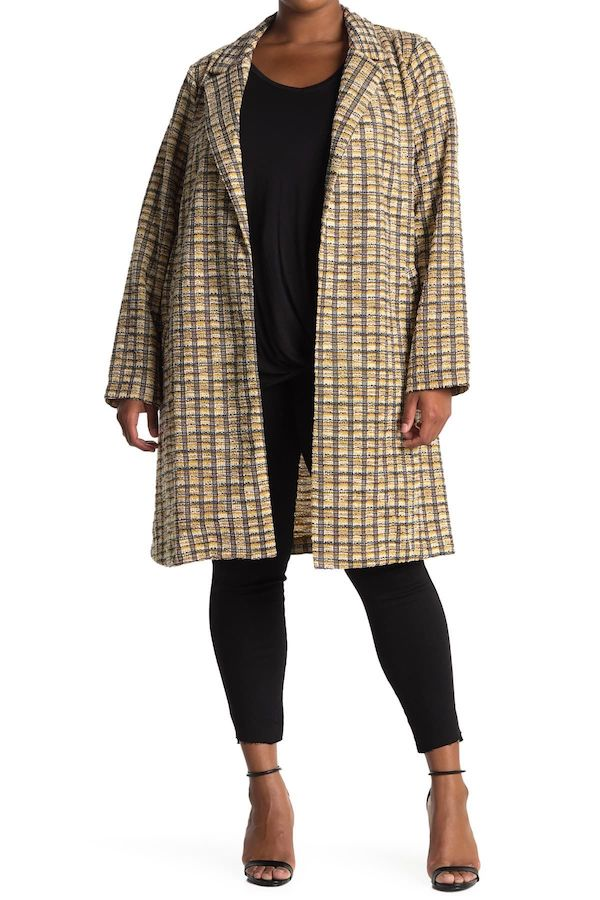 A plus-size model from Nordstrom Rack wearing a yellow and brown coat.