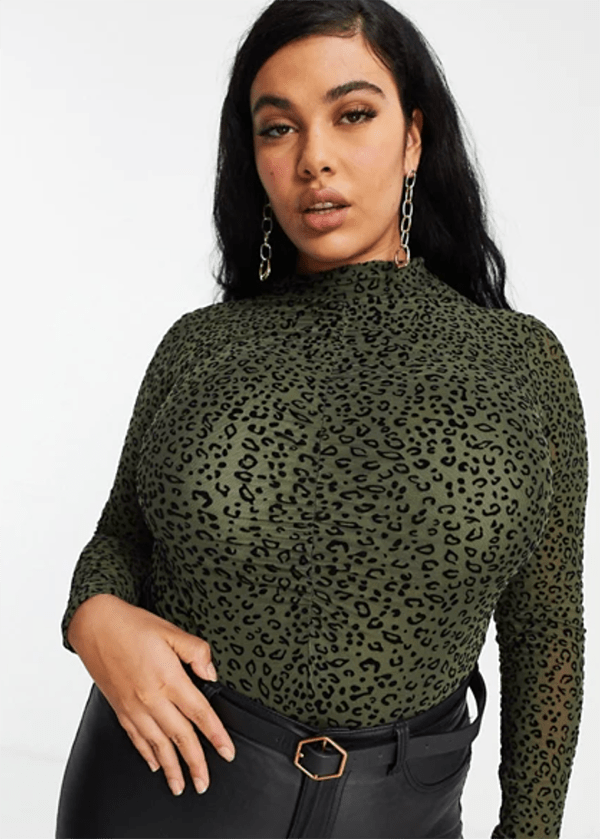 A plus-size model wearing an olive green animal print top, which is currently marked down at ASOS's 2020 Black Friday sale.