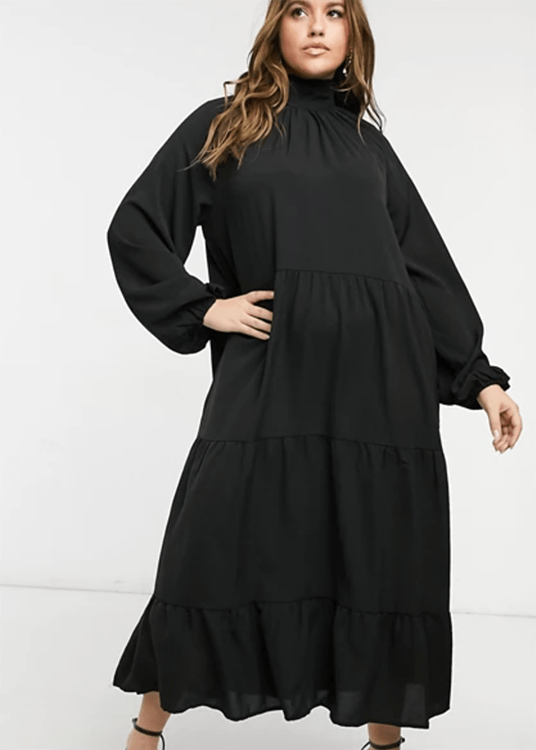 A plus-size model wearing a black dress, which is currently marked down at ASOS's 2020 Black Friday sale.