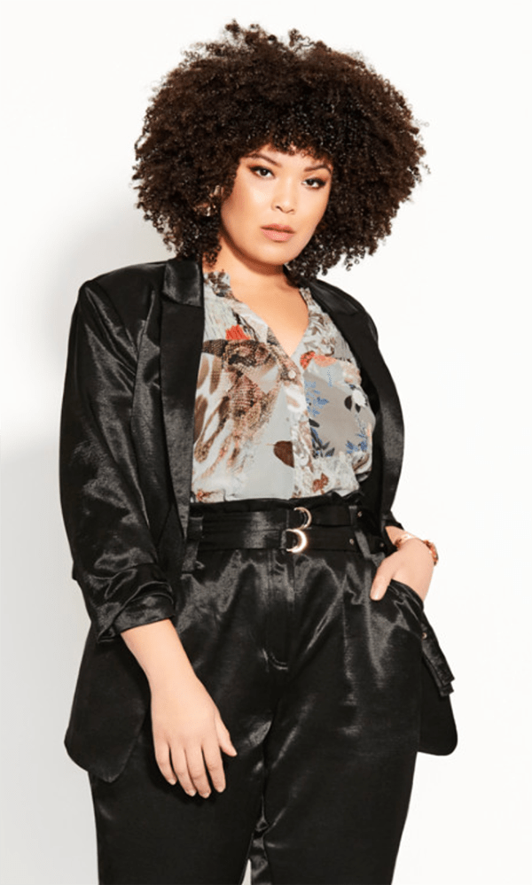 A plus-size model wearing a black satin blazer, which will be marked down at City Chic's 2020 Black Friday sale.