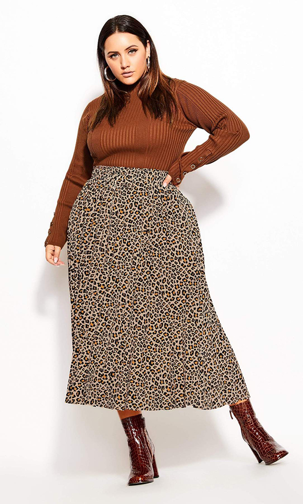 A plus-size model wearing a cheetah print midi skirt, which is currently marked down at CoEdition's 2020 Black Friday sale.
